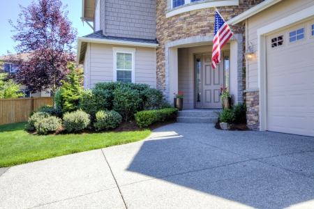 driveways: House beige exterior with driveway and American flag. Stock Photo