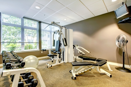 gym room: Gym in apartment building with brown wall and TV