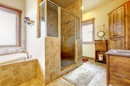 Large bathroom with wood furniture and natural colors.