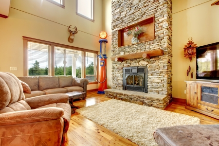 living room window: Living room with high ceiling, stone fireplace and leather sofa.
