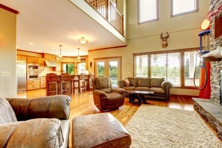 leren bank: Woonkamer met hoog plafond, stenen open haard en lederen sofa.