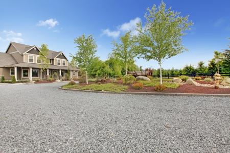 Gran finca con casa de campo camino de grava y el paisaje verde.
