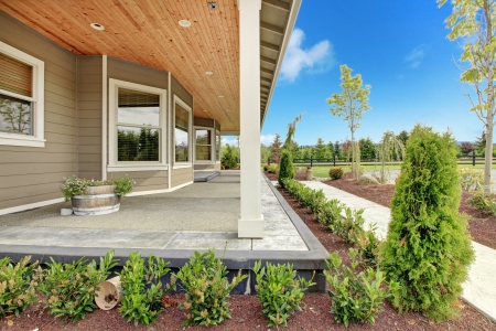 Large farm country house with long covered porch and green landscape.