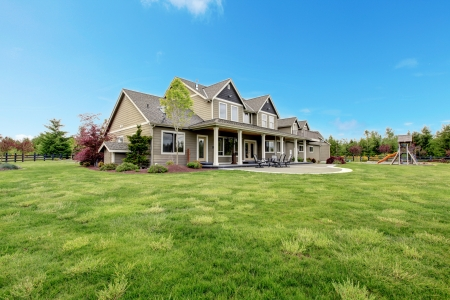front of house: Large farm country house with spring green landscape, kids play ground.
