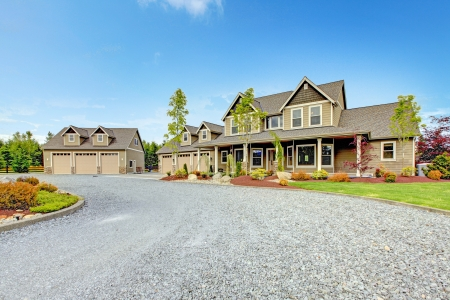 Large farm country house with gravel driveway and green landscape. photo