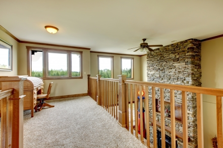 upstairs: House upstairs hallway with stone fireplace and wood railing. Stock Photo