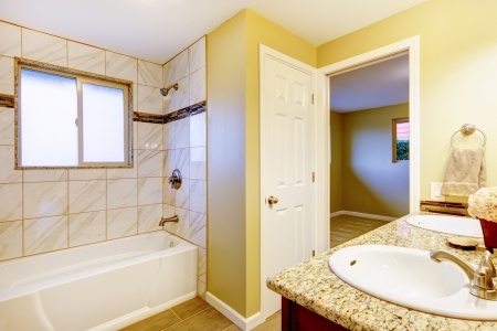 New bathroom interior with cherry sink cabinet and white tub  photo