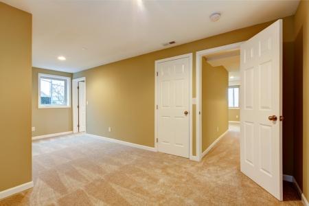 many doors: Empty new bedroom with many doors and beige carpet  Stock Photo