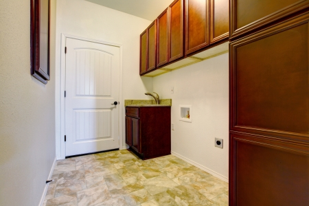New empty laundry room with wood cabinets, sink and tile floor. Stock Photo - 17869767