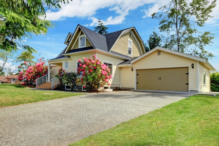 rhododendron: Yellow house exterior with spring blooming rhododendron Stock Photo