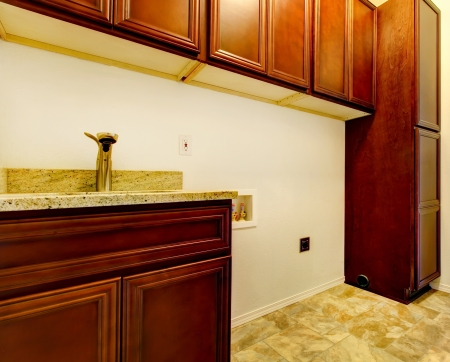 New empty laundry room with wood cabinets, sink and tile floor. Stock Photo - 17869698
