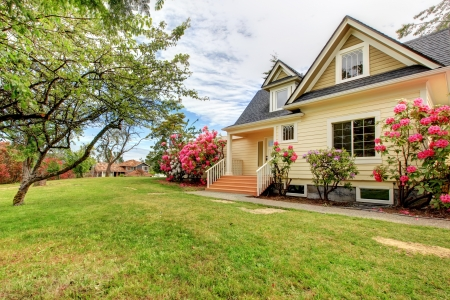 Yellow house exterior with spring blooming rhododendron Stock Photo - 17869771
