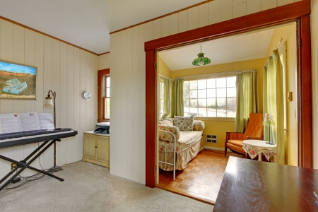 Small music room with sleeping sofa and reading corner in yellow and green. photo