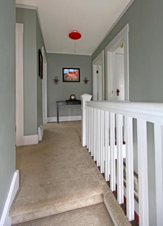 Grey upstairs hallway with white railing and beige carpet. Фото со стока