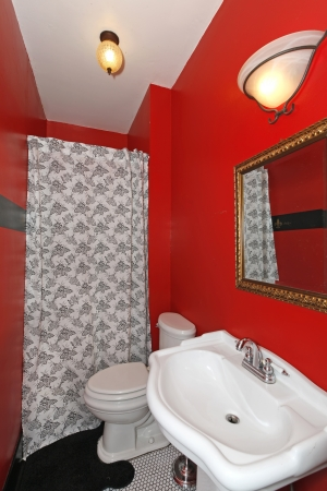 powder room: Red small bathroom with white sink and shower with black floor.