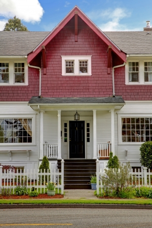 Classic large craftsman old American house exterior in red and white during spring. photo