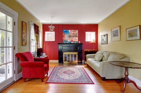 family sofa: Liviing room with red and yellow walls and fireplace in old American house.