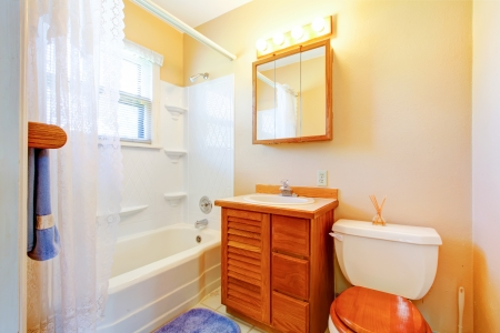 Small simple old bathroom with blue rug and wood cabinet. Stock Photo