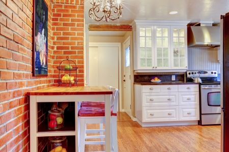 White kitchen with brick wall, hardwood and stainless steal stove with breakfast table. photo