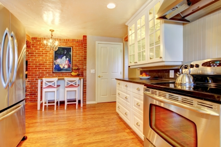 stainless steal: White kitchen with brick wall, hardwood and stainless steal stove and fridge.