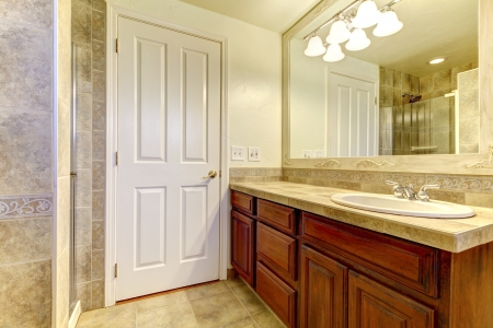 Bathroom with stone tiles and glass shower with wood cabinets.