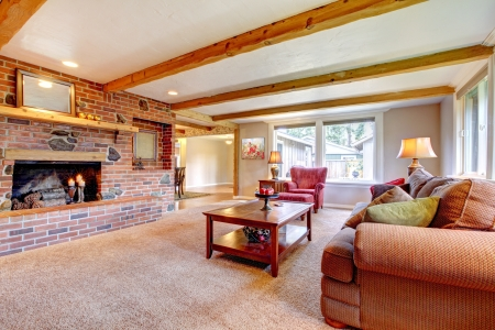 living room sofa: Living room interior with brick fireplace, wood beams and red.