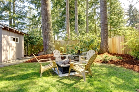 Home exterior Backyard with chairs and pine trees. Spring. Stock Photo - 18230677