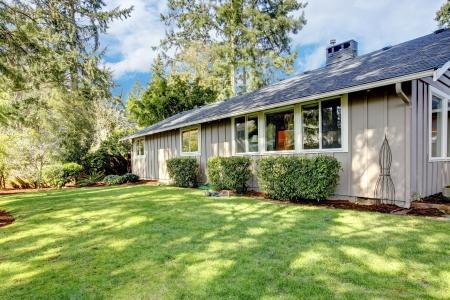 Brown grey house exterior with spring backyard. Stock Photo - 18230680