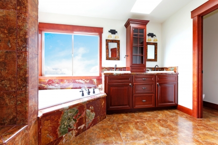 corner tub: Luxury new home bathroom with red marble and mahogany wood.