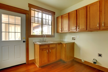 Laundry room with sink and wood cabinets.  New luxury home interior. Stock Photo - 18283807