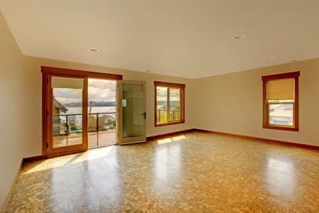 remodeled: Lage bright empty room with cork floor and balcony.New luxury home interior.