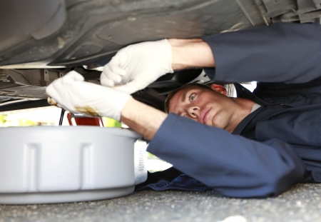 Man changing car oil laying under vehicle. photo