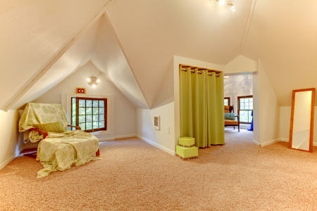 Attic room with chair, mirror and play room with clothes.
