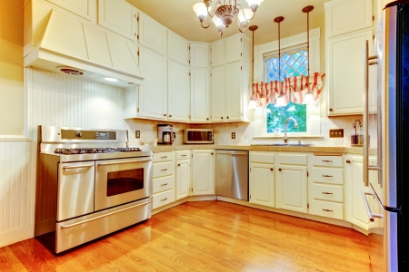 appliance: Large white kitchen in an old AMerican house with hardwood floor.