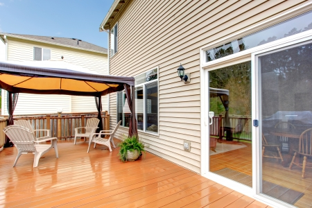 back yard: House Back porch with umbrella and chairs during rain. Stock Photo
