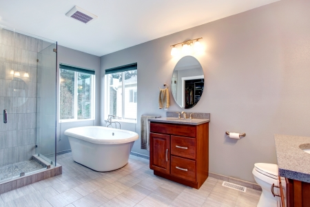 bathroom interior: Beautiful grey new modern bathroom interior with two separate sinks, tub and glass shower. Stock Photo
