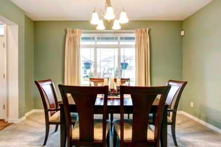 dining room: Green dining room interior with classic brown furniture and beige carpet.