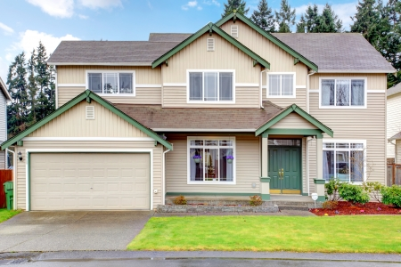 garage on house: Classic new Northwest American large house exterior with beige and green.