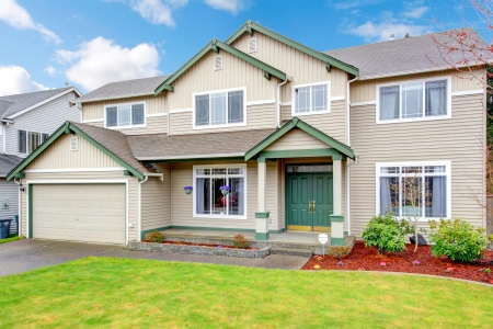 Classic new Northwest American large house exterior with beige and green.