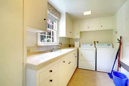 Laundry room with white old cabinets in large historical home. Stock Photo