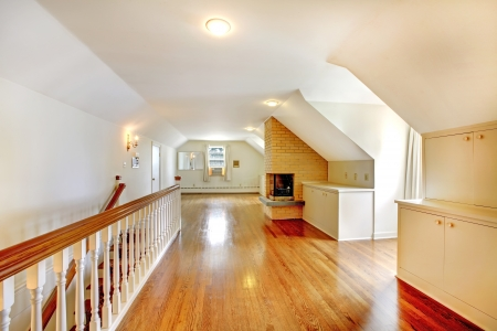 Large long attic room with fireplace. Empty with golden hardwood. Imagens