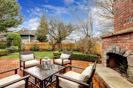 Spring fenced luxury  backyard with outdoor fireplace and furniture.