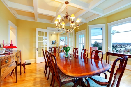 dining room: Golden bright yellow luxury dining room with elegant classic furniture and white wood ceiling. Stock Photo