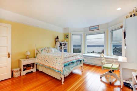 Tennage girl yellow bedroom interior with white furniture and hardwood floor.