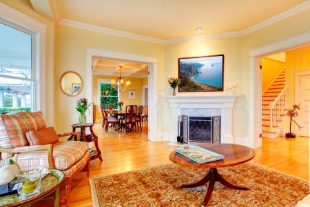твердая древесина: Золотой ярко-желтый гостиной роскоши с камином, диваном и ковром.