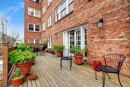 condominium complex: Brick apartment building large outdoor terrace.