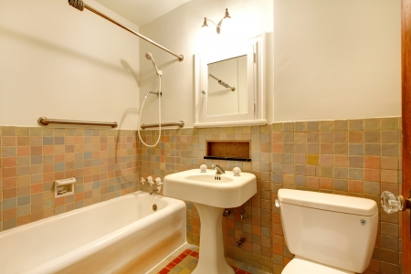 bathroom mirror: Apartment Bathroom with old antique fixtures and white tub. Stock Photo