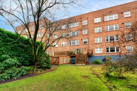 Brick large old apartment building with green spring backyard. Stock Photo - 20992937