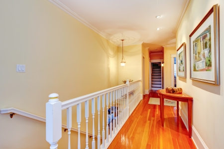 Hallway with hardwood floor and white railing to staircase. photo