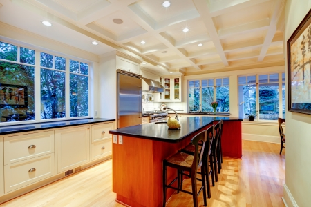 White large luxury kitchen with huge wood island and refrigerator. Stock Photo